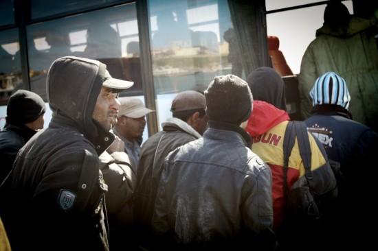 Migrantes da Tunísia, após quatro dias no mar, pegam ônibus em Lampedusa que os levaria a um centro de detenção